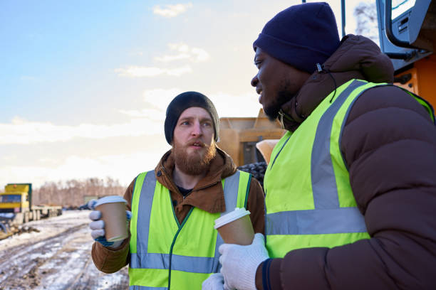 Tough Workers on Coffee Break Portrait of two workers, one African-American, drinking coffee and chatting next to heavy industrial truck on worksite, copy space frontier field stock pictures, royalty-free photos & images