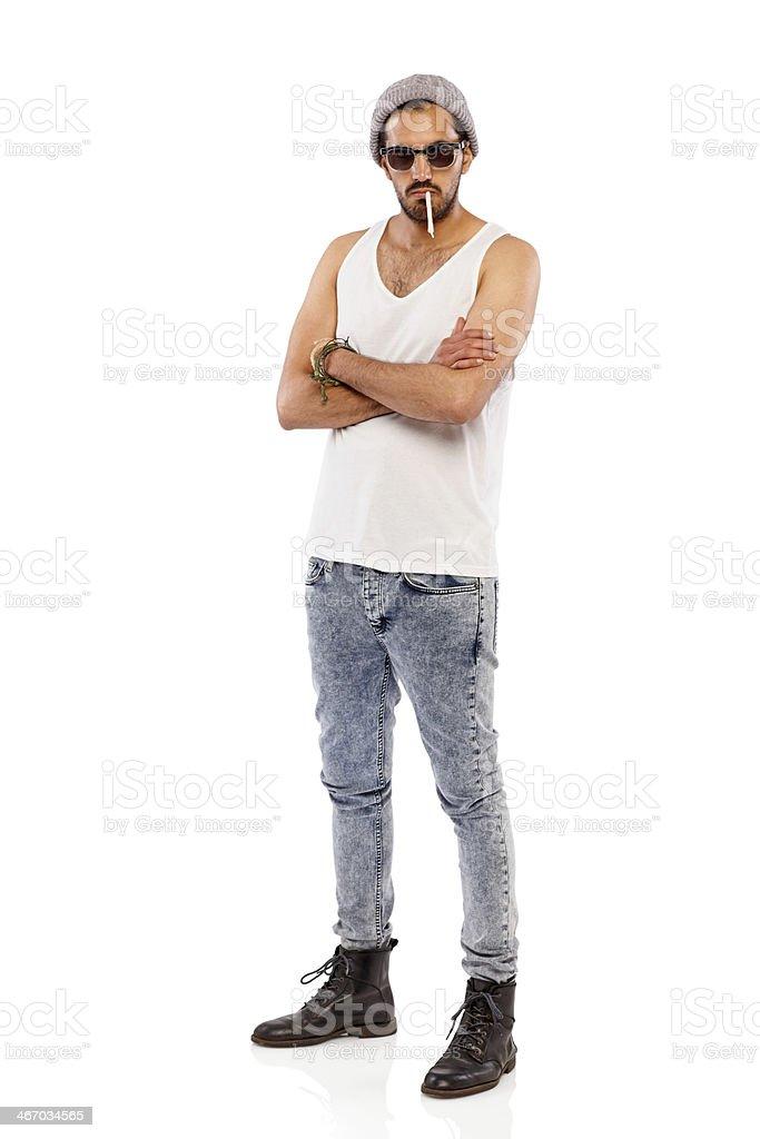 Tough young man smoking cigarette over white stock photo