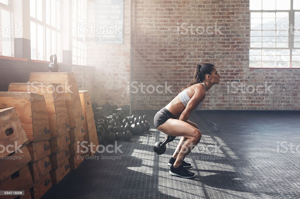 Tough young woman exercising with kettle bell at gym stock photo