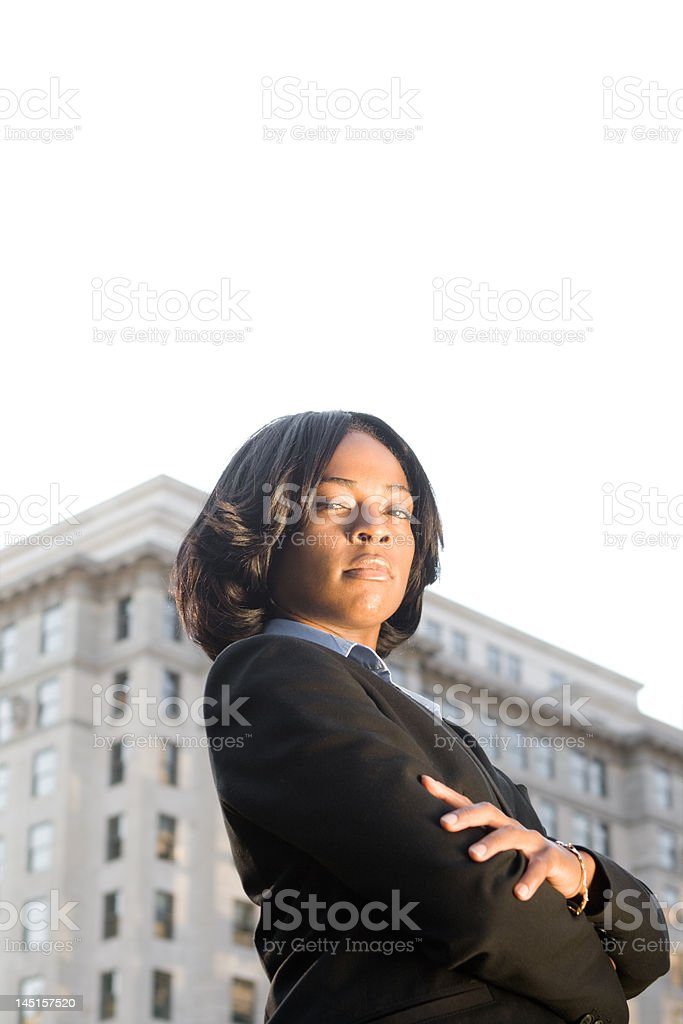 Tough-Looking African American Businesswoman, Arms Crossed, Office Building Background stock photo