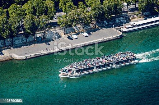 Tour boat on River Seine passing the Eiffel Tower, Paris, France