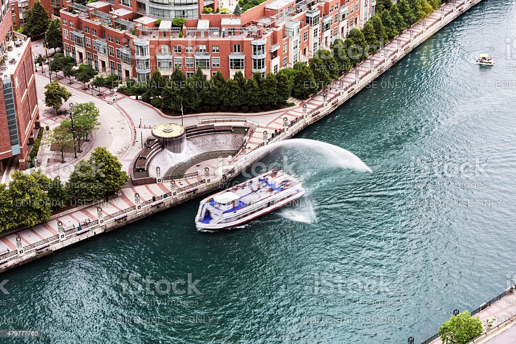 Tour boat passing under Centennial Fountain  water jet, Chicago stock photo
