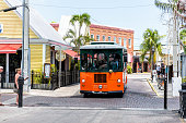 Key West, USA - May 1, 2018: Tour bus trolley in Florida island on travel, sunny day, architecture, street road with people