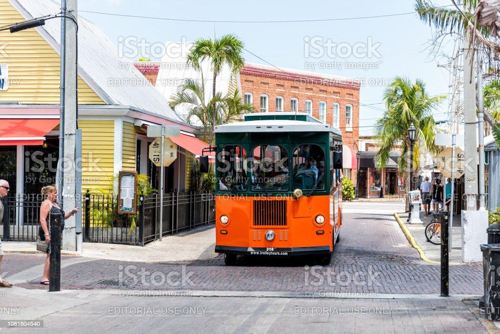 Trole de ônibus de turnê na ilha Florida no curso, dia ensolarado, arquitetura, rua estrada com pessoas - foto de acervo