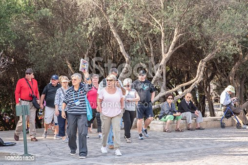 Athens, Greece - October 14, 2018: A tour guide holds up a sign indicating to follow her as she guides a group of older tourists toward the famous landmark, the Acropolis.