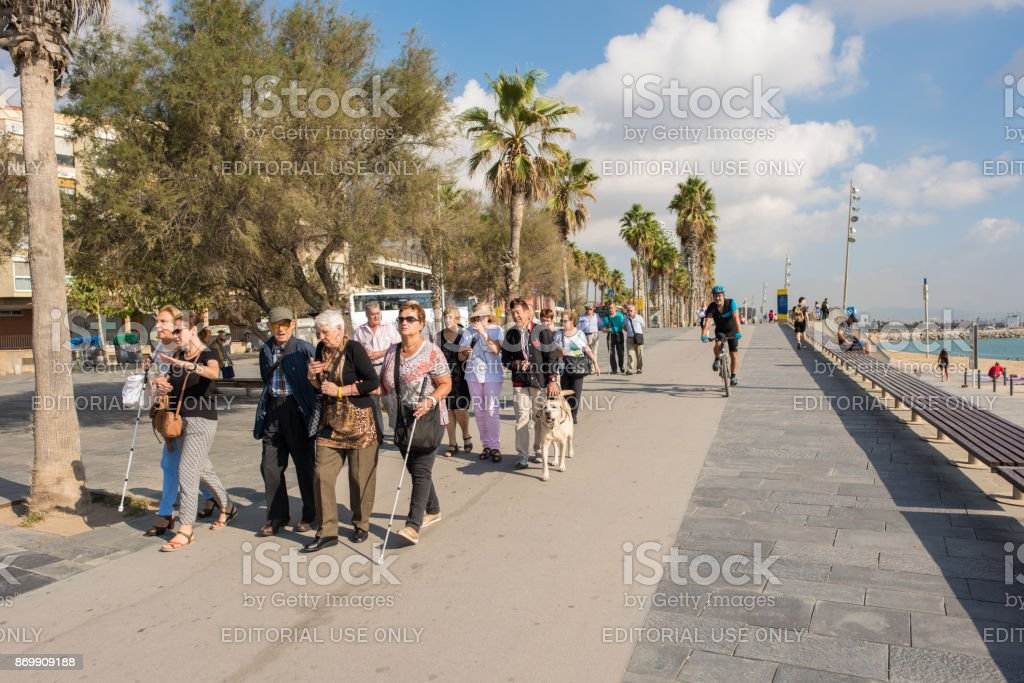Tour group going for a walk at the beach in Barceloneta, Barcelona stock photo