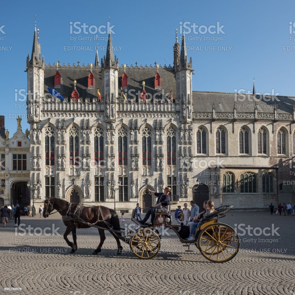 Tour guide and tourists on cart and horse in Bruges. stock photo