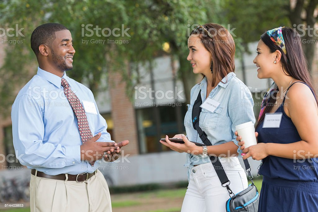 Tour guide talking to potential students while visiting campus stock photo