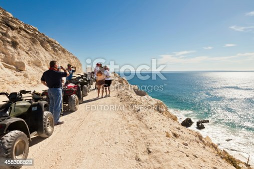 Cabo San Lucas, Mexico - February 12, 2011:  Guests of an ATV tour enjoy a rest and the coastline of the Sea of Cortez.  These ATV tours are very popular with visitors and take riders from the desert terrain to the sea.