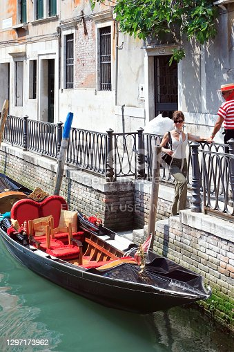 Venice. Italy - May 1, 2007: An attractive woman gets out of the gondola after touring Venice
