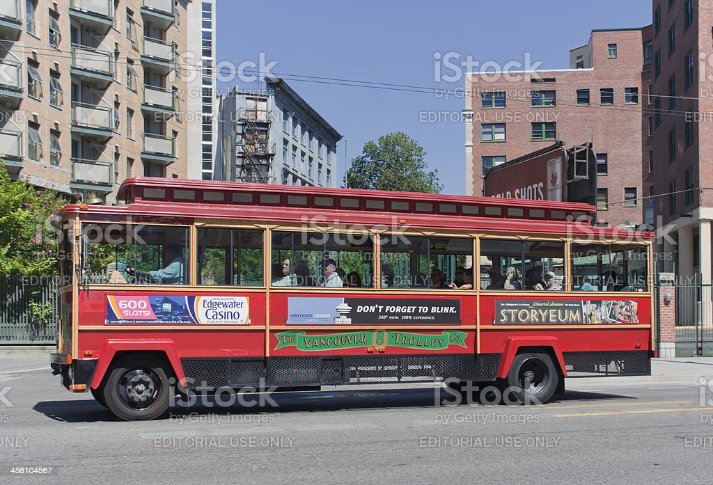 Tour Trolley Bus driving in front of Apartment Buildings stock photo