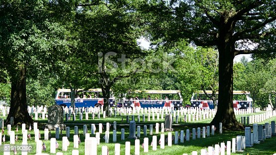 Arlington, Virginia, USA - May 24, 2015: Tourists ride past rows of tombstones with small American flags at Arlington National Cemetery at Fort Myer, Virginia, on Memorial Day weekend.