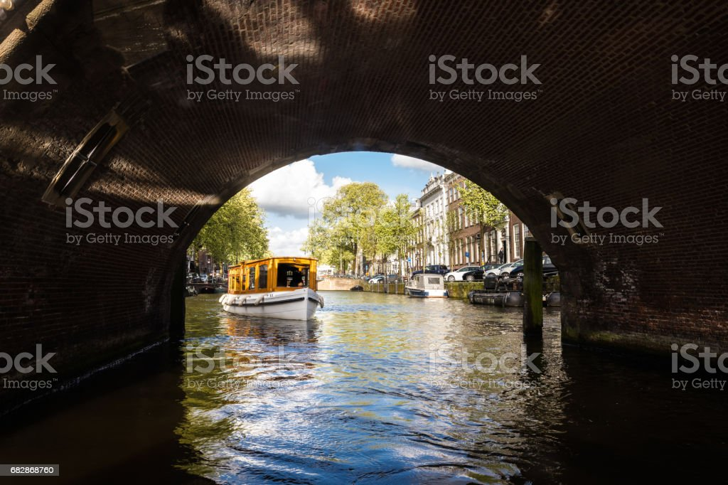 Tourboat about to go under a bridge on Amsterdam canal stock photo