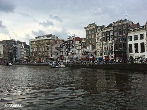 Amsterdam, The Netherlands - June 29, 2016: Tourists riding the tourboat in a canal to see the historical buildings and natural beauty of Amsterdam.