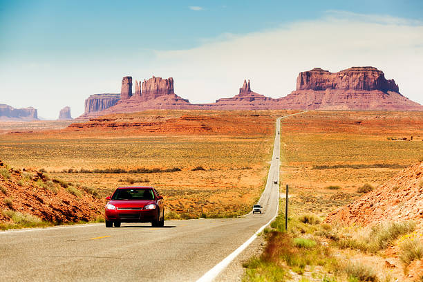 Touring the American Southwest, Monument Valley Highway with Cars Subject: Tourists in a red car traveling in the American Southwest, driving downhill on a straight length of highway stretching from southern Utah toward Monument Valley, Arizona colorado plateau stock pictures, royalty-free photos & images
