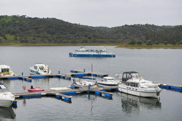 tourism boats on a marina pier of alqueva dam reservoir, in portugal - fotos de barragem portugal imagens e fotografias de stock