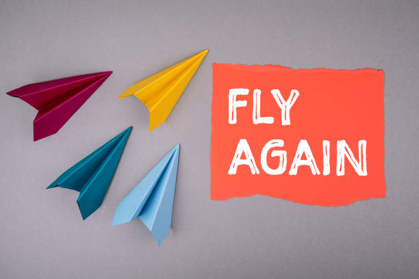 FLY AGAIN. Tourism, deregulation and the economy concept. Text on note sheet, paper planes around FLY AGAIN. Tourism, deregulation and the economy concept. Text on note sheet, paper planes around, symbol of gaining goals, striving upwards deregulation stock pictures, royalty-free photos & images