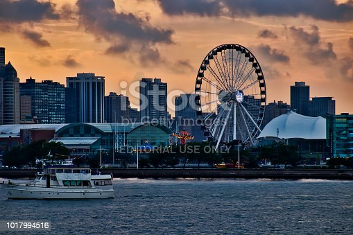 Tourism location of Navy Pier in Chicago along Lake Michigan, with tour boat passing in foreground during summer.