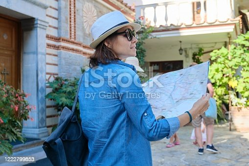 Tourism, woman visiting Christian monastery, historical monument in Greece in the mountains, female with map