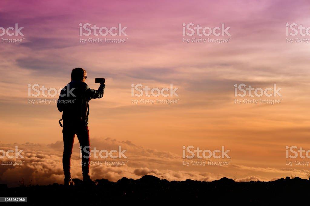 Tourist admiring breathtaking sunset views from the Mauna Kea, a dormant volcano on the island of Hawaii stock photo