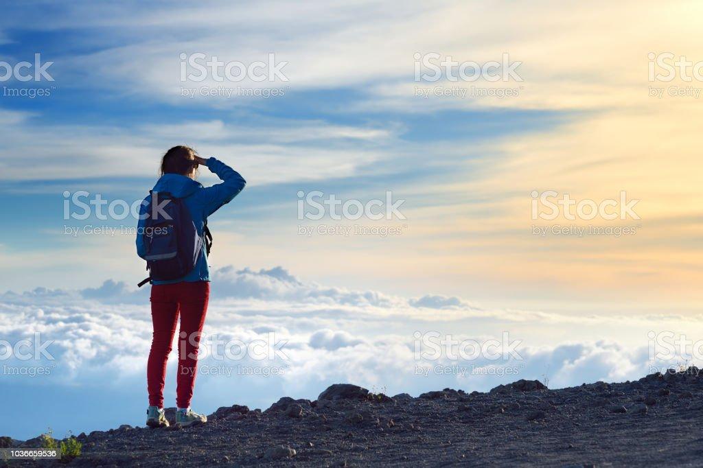 Tourist admiring breathtaking sunset views from the Mauna Kea, a dormant volcano on the island of Hawaii. stock photo