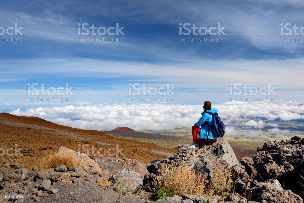 Tourist admiring breathtaking view of Mauna Loa volcano on the Big Island of Hawaii. stock photo