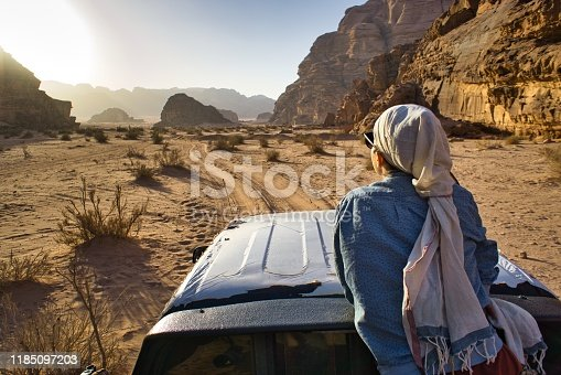 Wadi Rum, Jordan - October 20, 2017: A woman tourist sitting on a car and admiring the sun light in an opening between two hills in the desert, during day time, in Wadi Rum, Jordan.