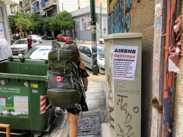 Un turista y un usuario de Airbnb pasando por delante de un anti-Airbnb publicado en la zona de Koukaki de Atenas, Grecia. - foto de stock