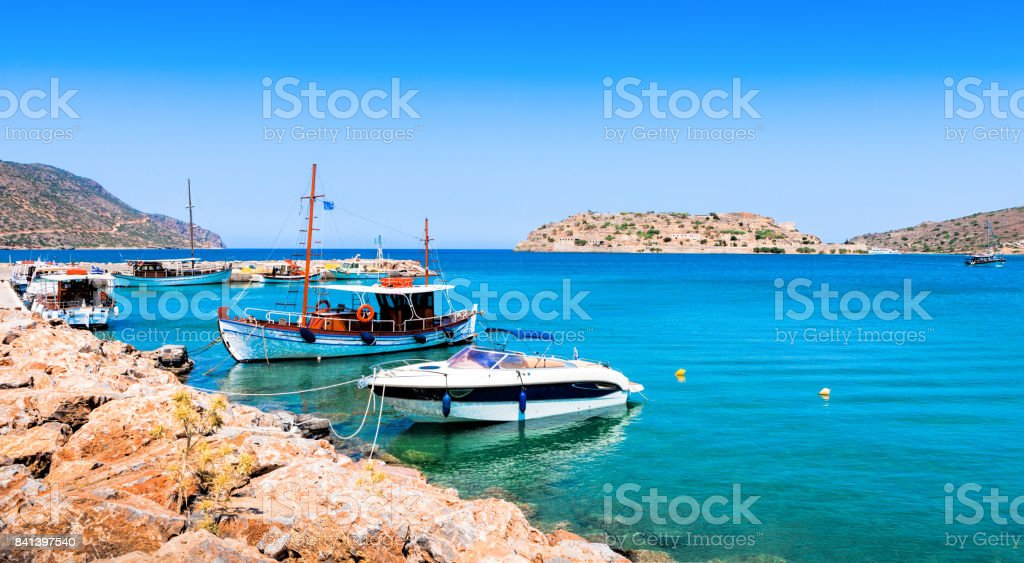 Tourist and fishing boats at the pier of the village of Plaka, near the island of Spinalonga. Crete stock photo