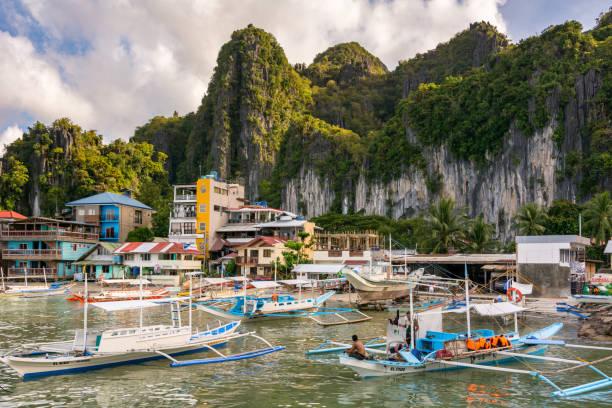 Touristen- und Fischerboote vor der Küste der Stadt El Nido – Foto