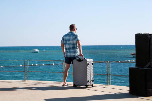 O turista e o viajante são carrinho na praia do recurso do hotel com mala de viagem viajado, aprecia o ambiente do mar da vista, paisagem da natureza, panorama, horizonte e descanso no sol. Homem considerável em férias no verão. - foto de acervo