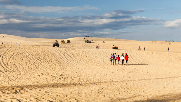 Tourist and vehicles on yellow sand dunes in Mui Ne, Vietnam stock photo