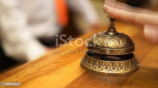 840883328 istock photo Tourist arrival at hotel. Modern luxury hotel reception counter desk with hand ringing the bell 1158794322