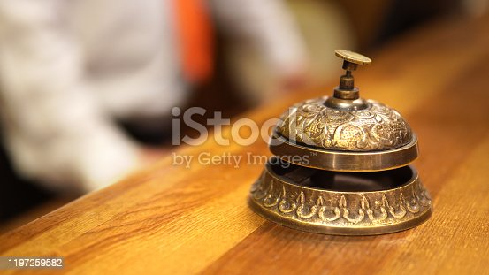 840883328 istock photo Tourist arrival at hotel. Modern luxury hotel reception counter desk with hand ringing the bell 1197259582