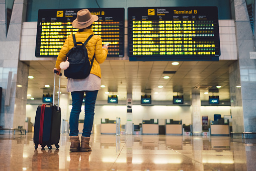 Young woman at the airport in Barcelona checking for the flight schedule