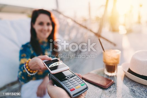 Smiling woman in hammock making mobile payment for drinks