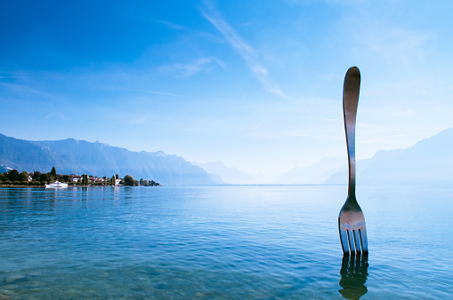 Tourist at Lake Geneva shore with The Fork of Vevey modern installation art