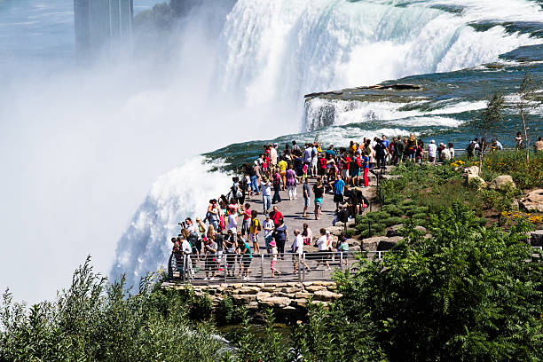 tourist at niagara falls niagra Falls, USA - august 10, 2013:people and tourists admire the falls on the American side from one of the many places of scenic path in a sunny day rainbow bridge ontario stock pictures, royalty-free photos & images