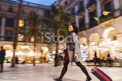 Woman with suitcase enjoying Barcelona at night