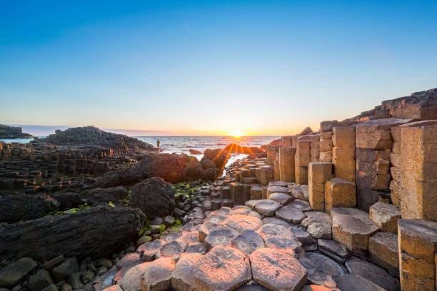 tourisme au coucher du soleil sur la chaussée des géants, irlande du nord - irlande photos et images de collection