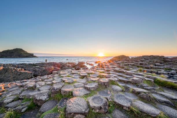 Turismo en puesta de sol sobre la calzada del gigante, Irlanda del norte - foto de stock