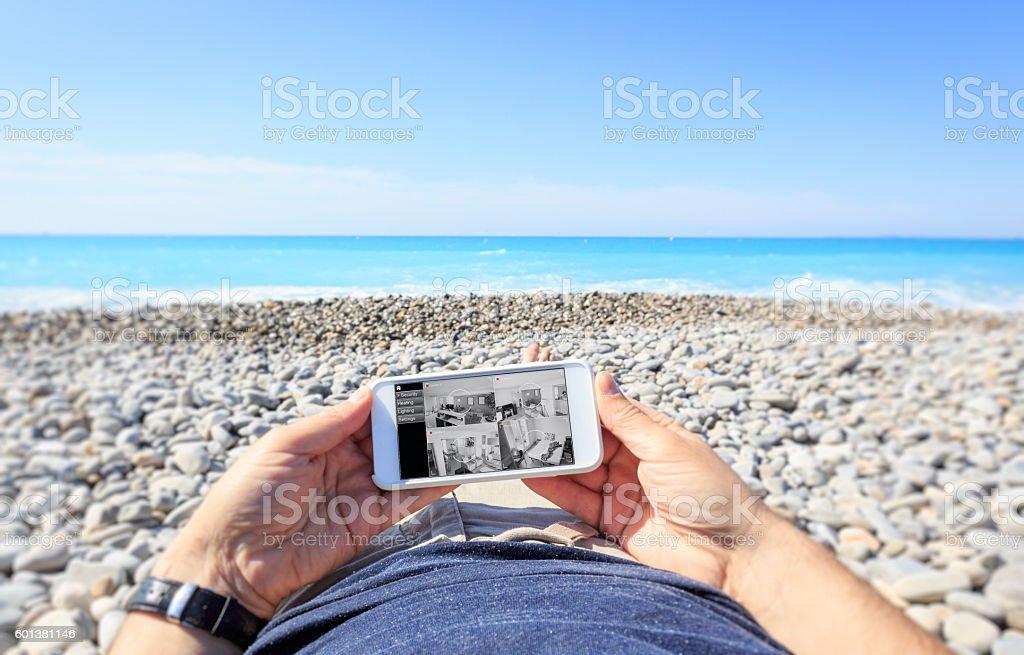Tourist at the beach checking surveillance cameras at home foto