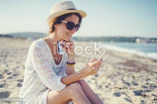 Relaxed woman on vacation online banking on smartphone