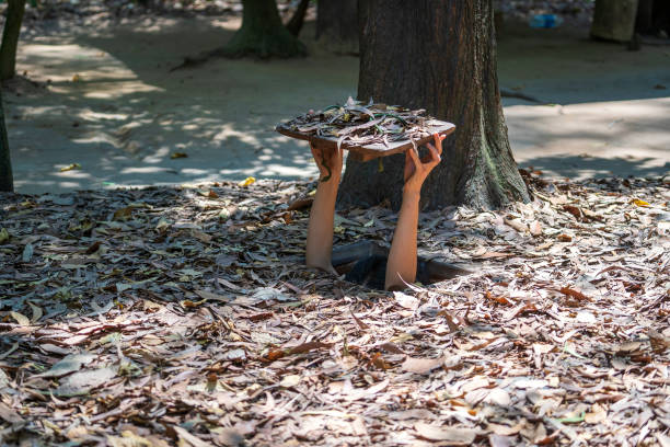 Tourist at the entrance of Cu Chi Tunnels in Ho Chi Minh, Vietnam, closeup Tourist at the entrance of Cu Chi Tunnels in Ho Chi Minh, Vietnam, close up viet cong stock pictures, royalty-free photos & images