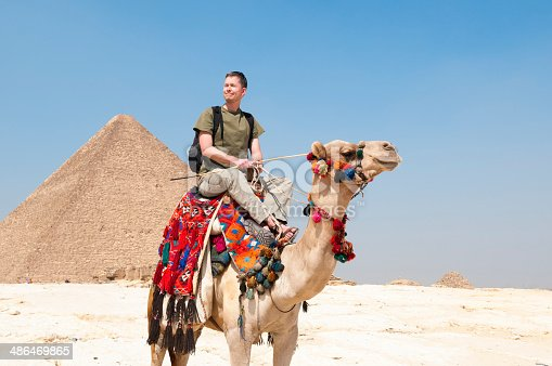 A tourist views the Pyramids of Giza from atop a camel in Cairo, Egypt
