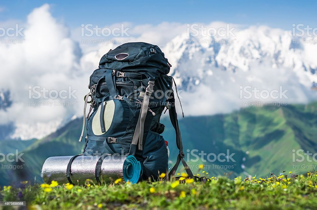 Tourist backpack and sleeping pad on a background of mountains stock photo