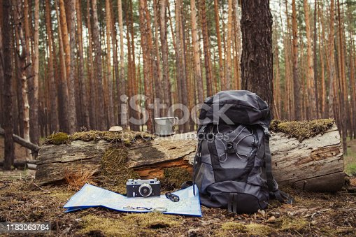 Tourist backpack, metal mug, camera and map in the forest. Concept of a hiking trip to the forest or mountains.