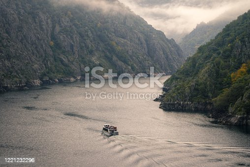 A tourist boat crosses the river entering Granitic Canyons in the Ribeira Sacra between Lugo and Ourense