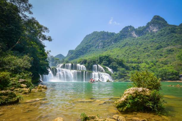 Tourist boat cruising on the water of beautiful waterfall in Vietnam stock photo