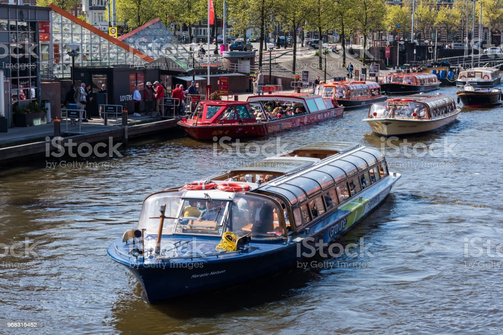 Tourist boat on Amsterdam canal, Nederlands stock photo